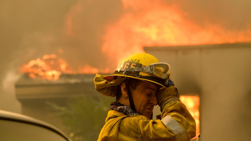 A firefighter keeps watch as the wildfire burns a home near Malibu Lake in Malibu, Calif., Friday, Nov. 9, 2018. (AP Photo/Ringo H.W. Chiu, File)