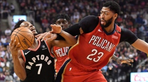 Toronto Raptors guard Kyle Lowry (7) and New Orleans Pelicans forward Anthony Davis (23) battle for the ball during first half NBA basketball action in Toronto on Monday, November 12, 2018. THE CANADIAN PRESS/Nathan Denette