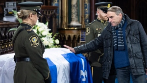 Actor Pierre Chagnon touches the casket of former Quebec premier Bernard Landry, who died last week, during a public viewing in Montreal on Monday, November 12, 2018. THE CANADIAN PRESS/Paul Chiasson