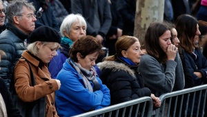 People pay respect to the victims during a ceremony marking the third anniversary of the Paris attacks of November 2015 in which 130 people were killed, in Paris, Tuesday, Nov. 13, 2018. (AP Photo/Christophe Ena)