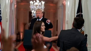 FILE - In this Nov. 7, 2018 file photo, President Donald Trump watches as a White House aide reaches to take away a microphone from CNN journalist Jim Acosta during a news conference in the East Room of the White House in Washington. C (AP Photo/Evan Vucci, File)