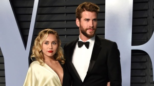 In this March 4, 2018 file photo, Miley Cyrus, left, and Liam Hemsworth arrive at the Vanity Fair Oscar Party in Beverly Hills, Calif. Though Cyrus and Hemsworth lost their home in the deadly wildfire blazing California, they are donating $500,000 to The Malibu Foundation through Cyrus' charity, The Happy Hippie Foundation. (Photo by Evan Agostini/Invision/AP, FIle)