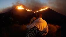 Roger Bloxberg, right, and his wife Anne hug as they watch a wildfire on a hill top near their home Friday, Nov. 9, 2018, in West Hills, Calif. (AP Photo/Marcio Jose Sanchez, File)