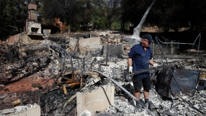 "Roger Kelton searches through the remains of his mother-in-law's home consumed by the Woolsey Fire Tuesday, Nov. 13, 2018, in Agoura Hills, Calif. ""We saw the pictures Friday of the house on fire,"" said Kelton. ""We knew it was gone but still haven't had my good cry yet. I've been trying to be strong for my daughter, my wife and my mother-in-law."" (AP Photo/Jae C. Hong)"