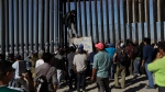 Central American migrants and others look on along the border structure, in Tijuana, Mexico Wednesday, Nov. 14, 2018. Migrants in a caravan of Central Americans scrambled to reach the U.S. border, catching rides on buses and trucks for hundreds of miles in the last leg of their journey Wednesday as the first sizable groups began arriving in the border city of Tijuana. (AP Photo/Gregory Bull)