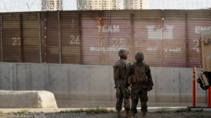 Marines look on during work to fortify the border structure that separates Tijuana, Mexico, behind, and San Diego, near the San Ysidro Port of Entry, Friday, Nov. 9, 2018, in San Diego. The military along the California border with Mexico worked Friday to fortify the border structure, including adding concertina wire to the tops of the rusting wall of corrugated metal. The military is expected to have the vast majority of the more than 7,000 troops planned for the mission along the border deployed by Monday, and that number could grow. (AP Photo/Gregory Bull)
