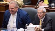 Vic Fedeli, right, Ontario Minister of Finance reads notes before tabling the government's Fall Economic Statement for 2018-2019 at Queen's Park in Toronto on Thursday, November 15, 2018. THE CANADIAN PRESS/Nathan Denette
