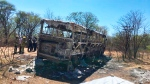 Emergency services stand near to a burnt out bus after a bus accident in Gwanda about 550 kilometres south of the capital Harare, Friday, Nov. 16, 2018. Police in Zimbabwe say more than 40 people have been killed in a bus accident on Thursday night. (AP Photo)