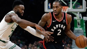 Toronto Raptors forward Kawhi Leonard (2) handles the ball against the defense of Boston Celtics guard Jaylen Brown in the first quarter of an NBA basketball game, Friday, Nov. 16, 2018, in Boston. (AP Photo/Elise Amendola)