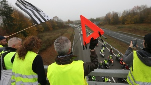Demonstrators salute drivers blocking road in Rennes, western France, Tuesday, Nov. 17, 2018, to protest against rising fuel taxes. France is bracing for a nationwide traffic mess as drivers plan to block roads to protest rising fuel taxes, in a new challenge to embattled President Emmanuel Macron. (AP Photo/David Vincent)