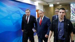 Israeli Prime Minister Benjamin Netanyahu, center, arrives for the weekly cabinet meeting at the prime minister's office in Jerusalem, Sunday, Nov. 18, 2018. (Abir Sultan/Pool via AP)