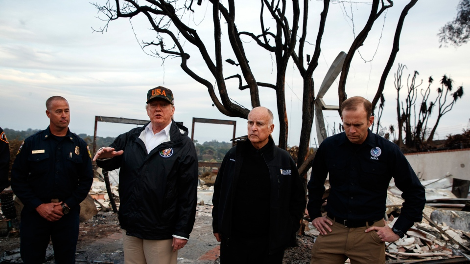 President Donald Trump visits a neighborhood impacted by the Woolsey Fire, Saturday, Nov. 17, 2018, in Malibu, Calif. At right is FEMA Administrator Brock Long and second from right is California Gov. Jerry Brown. (AP Photo/Evan Vucci)
