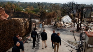 President Donald Trump visits a neighborhood impacted by the Woolsey Fire, Saturday, Nov. 17, 2018, in Malibu, Calif. (AP Photo/Evan Vucci)