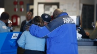 Chicago police department employees embrace with pastor Donovan Price, right, at 2nd District Headquarters, Tuesday, Nov. 20, 2018, in Chicago, the day after Officer Samuel Jimenez was killed at Mercy Hospital. (Jose M. Osorio/Chicago Tribune via AP)
