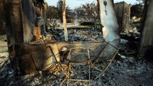 This Nov. 10, 2018 file photo shows a table and chairs outside one of at least 20 homes destroyed by the Woolsey fire on Wandermere Drive in the Point Dume area of Malibu, Calif. The number of structures destroyed by a huge Southern California wildfire has risen to 1,500. Another 341 structures were damaged as of a Monday, Nov. 20, 2018 count. As firefighters mop up, repair and restoration of utilities is continuing along with repopulation of areas evacuated when winds spread the fire earlier this month. Forecasters predict rain in the area by midweek. (AP Photo/Reed Saxon, File)