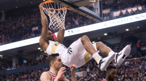 Toronto Raptors forward Kawhi Leonard hangs from the basket after scoring on the Washington Wizards during first half NBA basketball action in Toronto on Friday, November 23, 2018. THE CANADIAN PRESS/Chris Young