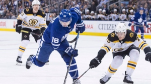 Toronto Maple Leafs' Mitchell Marner (16) tries to get a shot away as Boston Bruins defenseman Connor Clifton covers during second period NHL hockey action in Toronto on Monday, Nov. 26, 2018. THE CANADIAN PRESS/Chris Young