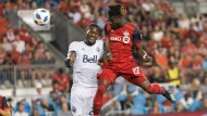 Toronto FC's Tosaint Ricketts, right, rises above Vancouver Whitecaps' Doneil Henry to score his team's fifth goal during second half action in the Canadian Championship Final's second leg in Toronto on Wednesday, August 15, 2018. THE CANADIAN PRESS/Chris Young