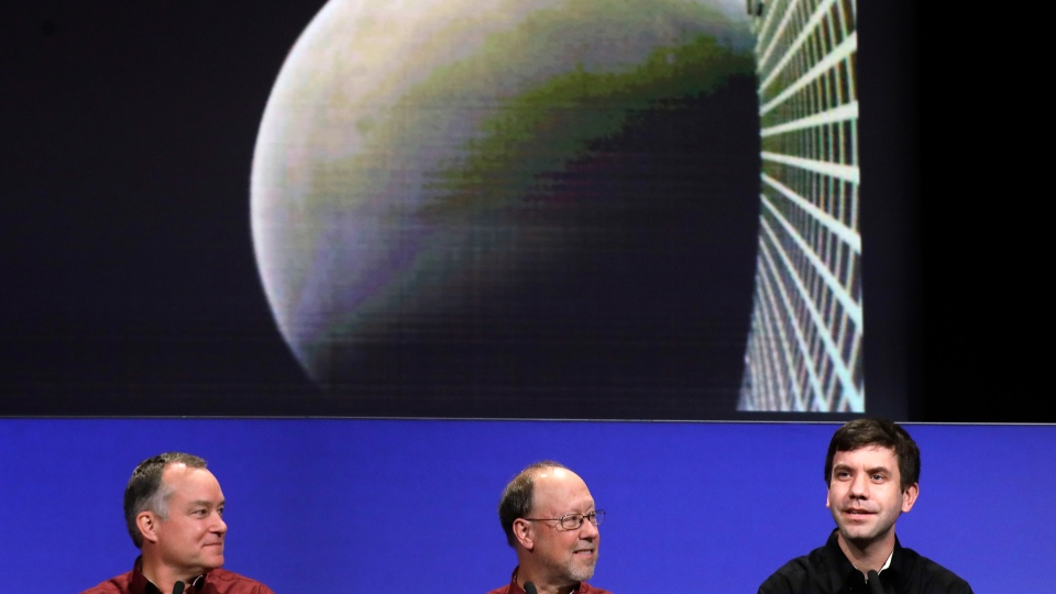 NASA official Andrew Klesh, right, speaks next to his colleagues, project manager Tom Hoffman, left, and lead scientist Bruce Banerdt, under a photograph taken by one of the mini satellites that was trailing the InSight lander, at NASA's Jet Propulsion Laboratory, Monday, Nov. 26, 2018, in Pasadena, Calif. (AP Photo/Marcio Jose Sanchez)