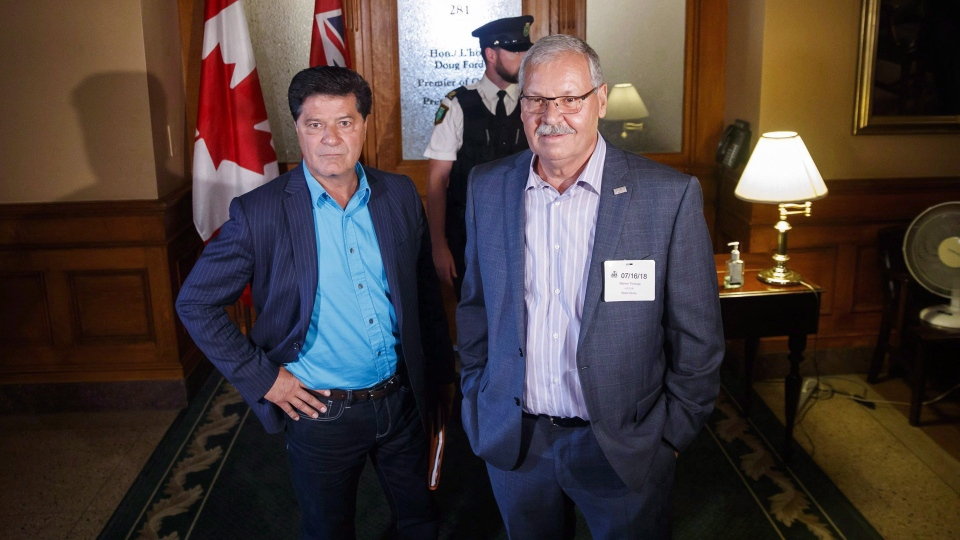 "President of Unifor Canada Jerry Dias, left, and Ontario Public Service Employees Union (OPSEU) president Warren (Smokey) Thomas wait outside Ontario Premier Doug Ford's office to request a meeting about the ""back-to-work"" legislation by the Ontario PC government, at Queen's Park, in Toronto, Monday, July 16, 2018. THE CANADIAN PRESS/Mark Blinch"