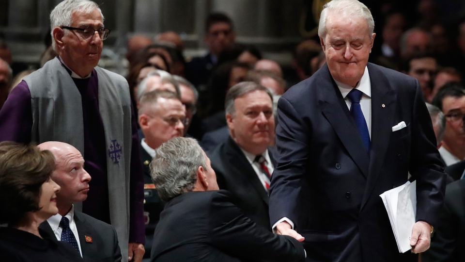 Former Canadian Prime Minister Brian Mulroney shakes hands with former President George W. Bush during the State Funeral for former President George H.W. Bush at the National Cathedral, Wednesday, Dec. 5, 2018, in Washington. (AP Photo/Alex Brandon, Pool)
