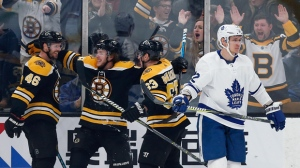 Boston Bruins' David Krejci (46) celebrates his goal with teammates Brad Marchand (63) and David Pastrnak as Toronto Maple Leafs' Nikita Zaitsev (22) skates away during the third period of an NHL hockey game in Boston, Saturday, Dec. 8, 2018. (AP Photo/Michael Dwyer)