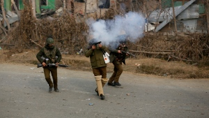 An Indian policeman fires a tear gas shell towards Kashmiri protesters near the site of a gun-battle in Mujagund area some 25 Kilometers (16 miles) from Srinagar, Indian controlled Kashmir, Sunday, Dec. 9, 2018. (AP Photo/Mukhtar Khan)