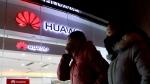 Women walk past a Huawei retail shop in Beijing Thursday, Dec. 6, 2018. (AP / Ng Han Guan)
