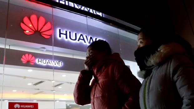 Women walk past a Huawei retail shop in Beijing Thursday Dec. 6 2018