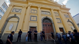 Police stand guard outside the Metropolitan Cathedral after a deadly shooting in Campinas, Brazil, Tuesday, Dec. 11, 2018. (AP Photo/Victor R. Caivano)