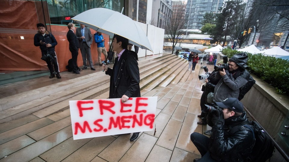 A supporter carries a sign outside B.C. Supreme Court during the third day of a bail hearing for Meng Wanzhou, the chief financial officer of Huawei Technologies, in Vancouver, on Tuesday December 11, 2018. THE CANADIAN PRESS/Darryl Dyck