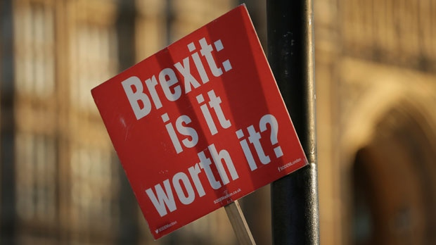 An anti-Brexit placard is tied to a lamppost outside the Houses of Parliament, in London, Wednesday December 12, 2018. British Conservative lawmakers forced a no-confidence vote in Prime Minister Theresa May for Wednesday, throwing U.K. politics deeper into crisis and Brexit further into doubt. (AP Photo/Tim Ireland)