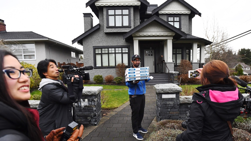 A pizza delivery man delivers pizza to the media after being instructed to do so by people inside of Huawei chief financial officer Meng Wanzhou's home in Vancouver on Wednesday, December 12, 2018. THE CANADIAN PRESS/Jonathan Hayward