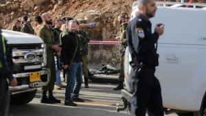 Israeli soldiers and emergency services stand at the scene of an attack near the settlement of Givat Assaf in the West Bank, Thursday, Dec. 13, 2018. A Palestinian gunman opened fire at a bus stop outside a West Bank settlement on Thursday, shooting at soldiers and civilians and killing at least two Israelis before fleeing, the military and Israel's rescue service said. (AP Photo/Mahmoud Illean)