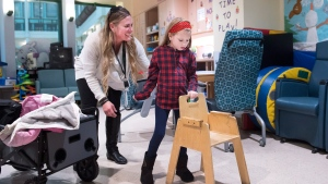 Nine-year-old Andi Dreher gets help walking from her mother Lori Dreher at SicKids after doctors at SickKids and Toronto Western Hospital performed Canada's first deep brain stimulation (DBS) to treat drug-resistant paediatric epilepsy on a child in Canada in Toronto on Wednesday, December 12, 2018. THE CANADIAN PRESS/Nathan Denette