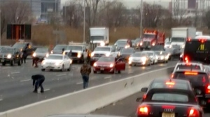 This screen shot from a video provided by Danielle Shah shows people picking up cash that spilled from an armored truck onto the highway in East Rutherford, N.J., near MetLife Stadium, Thursday, Dec. 13, 2018. Police say the incident caused multiple crashes as motorists stopped to grab the money from the truck that authorities say apparently had an issue with the locking device on one of its doors. (Danielle Shah/@dbholden417 via AP)