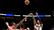 Portland Trail Blazers guard Damian Lillard, right, hits a shot over Toronto Raptors forward CJ Miles, left, and guard Fred VanVleet, center, during the second half of an NBA basketball game in Portland, Ore., Friday, Dec. 14, 2018. The Blazers won 128-122. (AP Photo/Steve Dykes)