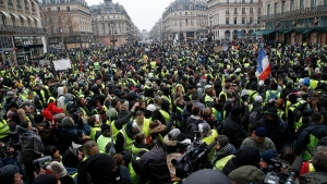 "Demonstrators gather during a protest outside the Opera house, Saturday, Dec. 15, 2018 in Paris. Paris police deployed in large numbers Saturday for the fifth straight weekend of demonstrations by the ""yellow vest"" protesters, with authorities repeating calls for calm after protests on previous weekends turned violent. (AP Photo/Michel Euler)"