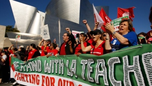 United Teachers Los Angeles leaders are joined by thousands of teachers, who may go on strike against the nation's second-largest school district next month, as they march past the Walt Disney Concert Hall in downtown Los Angeles Saturday, Dec. 15, 2018. (AP Photo/Damian Dovarganes)