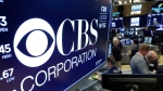 In this July 30, 2018, photo the logo for CBS Corporation is displayed above a trading post on the floor of the New York Stock Exchange. (AP Photo/Richard Drew, File)