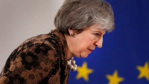 British Prime Minister Theresa May walks by the EU stars as she arrives for a media conference at an EU summit in Brussels, Friday, Dec. 14, 2018. European Union leaders expressed deep doubts Friday that British Prime Minister Theresa May can live up to her side of their Brexit agreement and they vowed to step up preparations for a potentially-catastrophic no-deal scenario. (AP Photo/Alastair Grant)