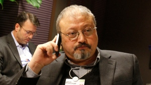 FILE - In this Jan. 29, 2011, file photo, Saudi Arabian journalist Jamal Khashoggi speaks on his cellphone at the World Economic Forum in Davos, Switzerland. Saudi Arabia issued an unusually strong rebuke of the U.S. Senate on Monday Dec. 17, 2018, rejecting a bipartisan resolution that put the blame for the killing of Saudi journalist Jamal Khashoggi squarely on the Saudi crown prince and describing it as interference in the kingdom's affairs. (AP Photo/Virginia Mayo, File)