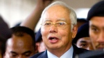FILE - In this Sept. 20, 2018, file photo, former Malaysian Prime Minister Najib Razak walks out of courtroom after a court hearing at Kuala Lumpur High Court in Kuala Lumpur, Malaysia. Malaysia says it has filed criminal charges against Goldman Sachs and two of its employees in connection with a multibillion-dollar scandal involving state investment fund 1MDB. Najib launched 1MDB in 2009 to promote economic development but it racked up billions of dollars in debts that have led to investigations in the U.S. and several other countries. (AP Photo/Yam G-Jun, FIle)