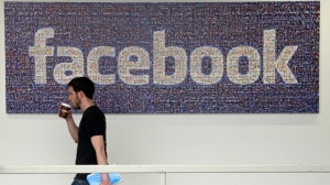 In this March 15, 2013, file photo, a man walks past a sign at Facebook headquarters in Menlo Park, California, USA.  Facebook gave some companies more extensive access to users' personal data than it has previously revealed, letting them read private messages or see the names of friends without consent, according to a New York Times report published Wednesday Dec. 19, 2018. (AP Photo/Jeff Chiu, File)