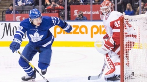 Toronto Maple Leafs Trevor Moore (left) skates past Detroit Red Wings goaltender Jonathan Bernier as he makes his NHL debut in Toronto, on Sunday, December 23, 2018.THE CANADIAN PRESS/Chris Young