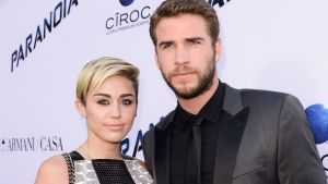 """In this Aug. 8, 2013, file photo, actor Liam Hemsworth and singer and actress Miley Cyrus arrive on the red carpet at the US premiere of the feature film """"Paranoia"""" at the DGA Theatre in Los Angeles. (Photo by Dan Steinberg/Invision/AP, File)"""