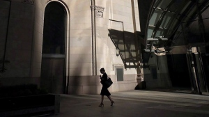 "A woman walks through Toronto's financial district on July 30, 2018. A new report looking at the country's highest-paid CEOs is adding new evidence to the argument that women face a ""double-pane glass ceiling"" at the top of Canada's corporate ladder -- first in getting in the executive suite and, once there, earning as much as their male counterparts. (THE CANADIAN PRESS/Graeme Roy)"