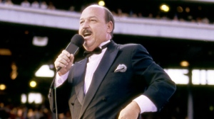 """In this July 31, 1988 photo provided by the WWE, """"Mean"""" Gene Okerlund addresses the crowd before a pro wrestling event in Milwaukee. (WWE via AP)"""
