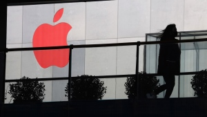 In this Dec. 6, 2018, photo, a woman runs past a Apple logo colored red in Beijing, China. (AP Photo/Ng Han Guan)