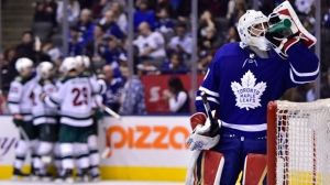 Toronto Maple Leafs goaltender Michael Hutchinson (30) takes a drink as Minnesota Wild players celebrate a goal by Zach Parise (11) during third period NHL hockey action in Toronto on Thursday, Jan.3, 2019. THE CANADIAN PRESS/Frank Gunn